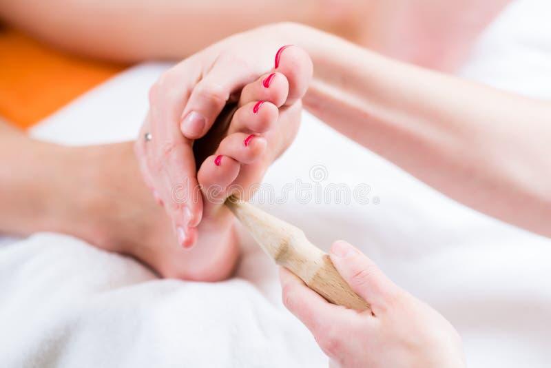 Women at reflexology having foot massaged stock image