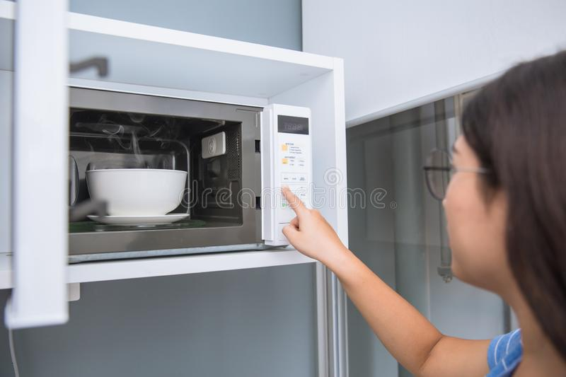 Women reheat food by using microwave oven with glass ceramic bowl royalty free stock photography