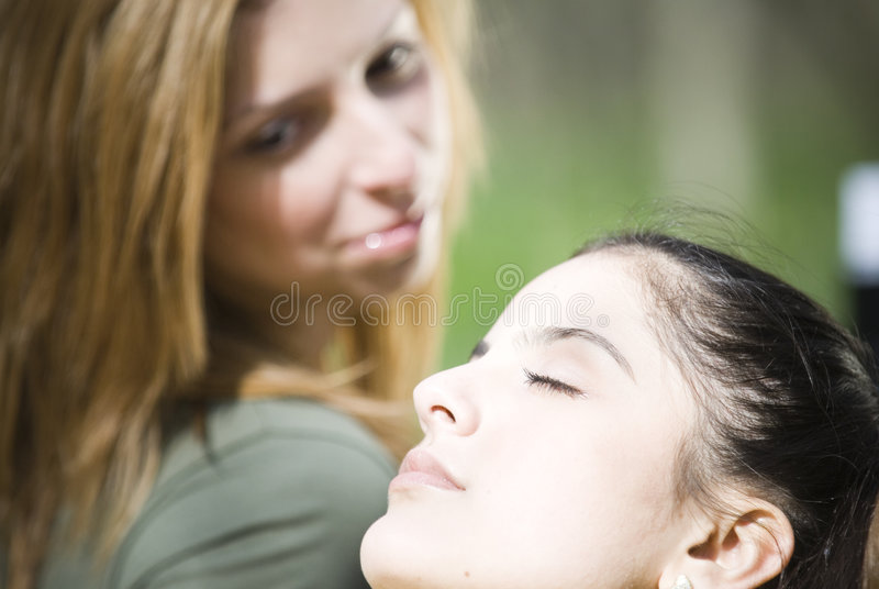 Women Relaxing. Closeup of two women relaxing. Focus is on woman in the foreground, who has her head leaning back and her eyes closed. Woman in the background is stock images