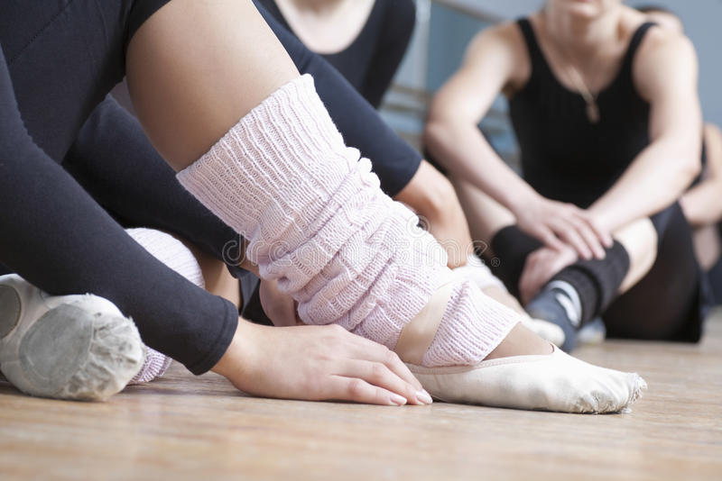 Women Relaxing In Ballet Rehearsal Room. Low section of women relaxing in ballet rehearsal room stock photo