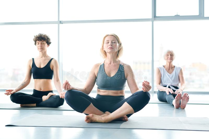 Women relaxing. Three barefoot active women sitting in pose of lotus with their eyes closed and keeping balance royalty free stock photos