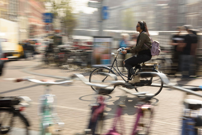 A Women Rides her bike to work in Amsterdam, Netherlands. stock photo