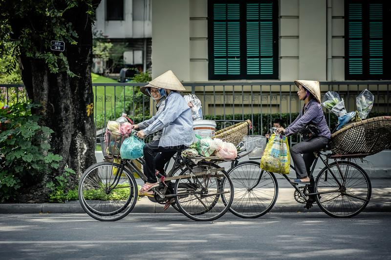 Women riding bicycles on the street in Hanoi. stock photography