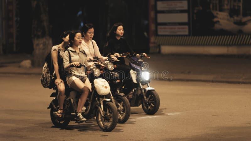 Women riding motorbikes. Young women riding motorbikes in Hanoi, Vietnam stock image