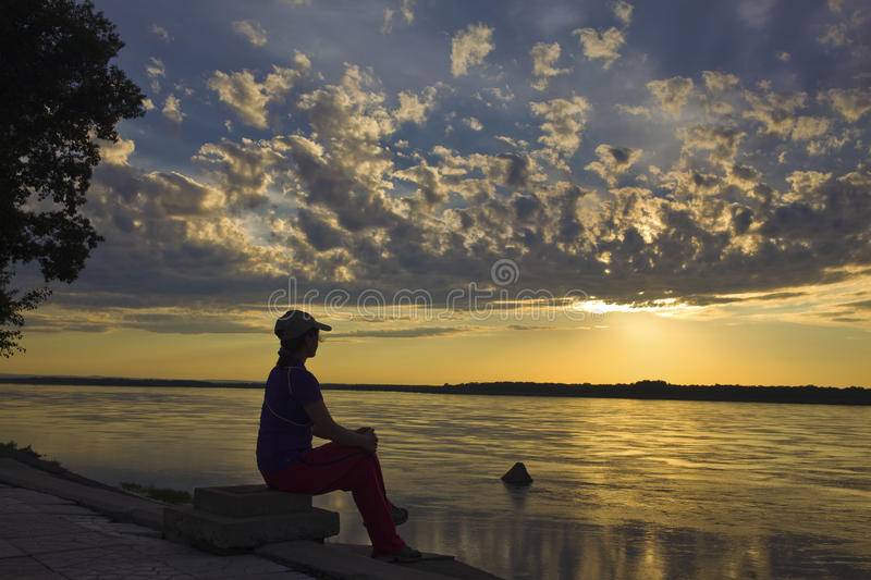 Women at river bank watching sunset stock photography