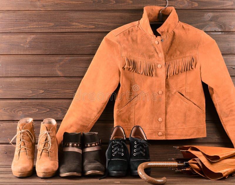 Women& x27; ropa y accesorios de s Chaqueta de la gamuza marrón, tres diversos pares de zapatos y paraguas foto de archivo libre de regalías