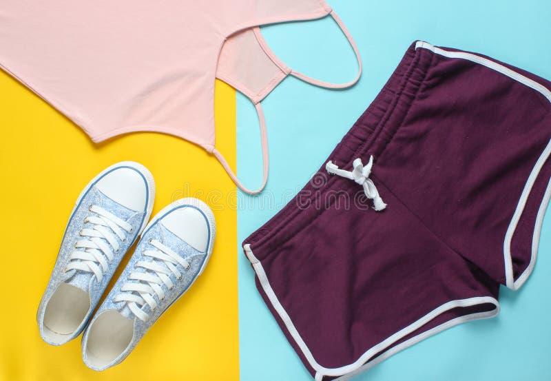 Women& x27; ropa y accesorios de s para la aptitud en un fondo en colores pastel coloreado Zapatilla de deporte, pantalones corto fotografía de archivo libre de regalías