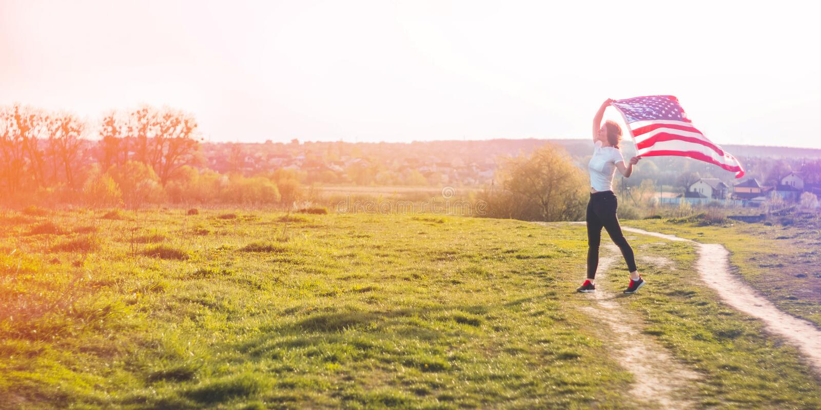Women running in the field with American flag USA celebrate 4th of July. Happy woman running in the field with American flag USA celebrate 4th of July royalty free stock photos