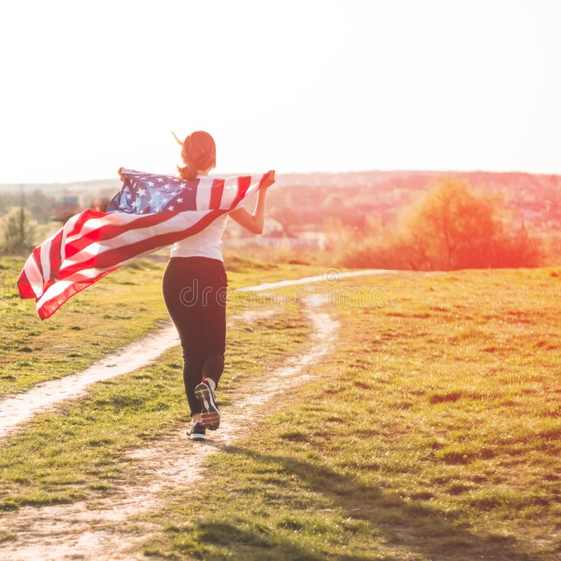 Women running in the field with American flag USA celebrate 4th of July. Happy woman running in the field with American flag USA celebrate 4th of July stock photos