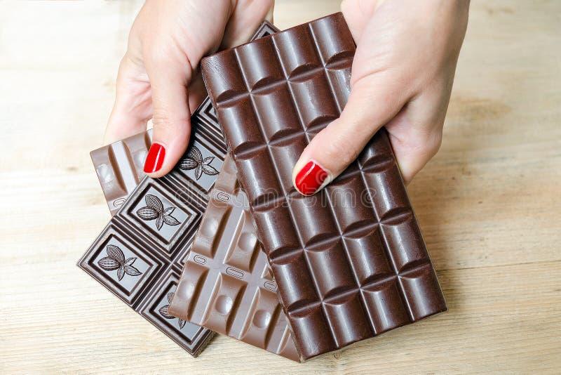 Women& x27; s手,提供不同的巧克力块选择-黑色,牛奶和多孔巧克力 免版税库存照片