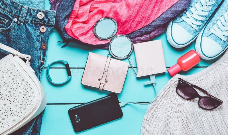 Women& x27; s时髦辅助部件、鞋子、衣裳和现代小配件在蓝色木背景 牛仔裤,袋子,运动鞋,智能手机 免版税库存图片