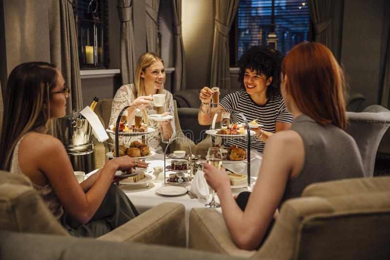 Women`s Afternoon Tea. Four women are sitting together enjoying afternoon tea. They are talking and eating and they have champagne and tea stock photo