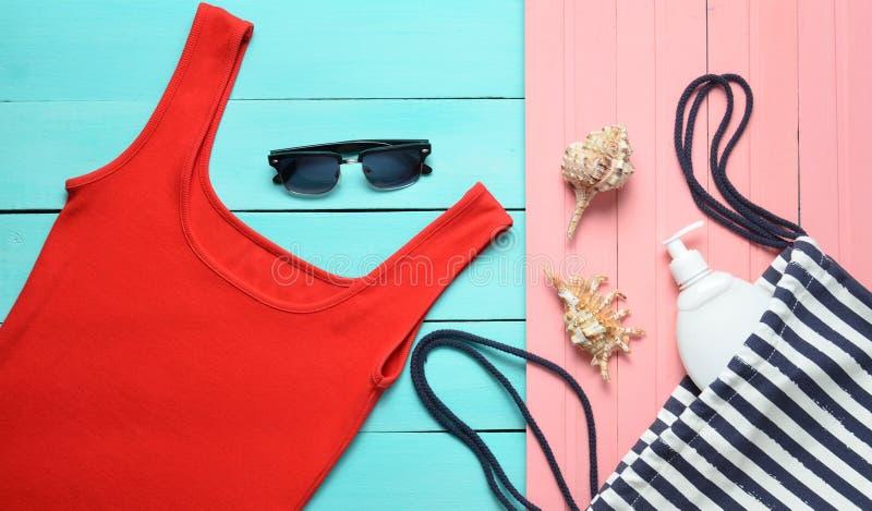 Women& x27; s akcesoria dla relaksu na plaży na drewnianym pastelowym tle i odzież koszula t zdjęcie royalty free