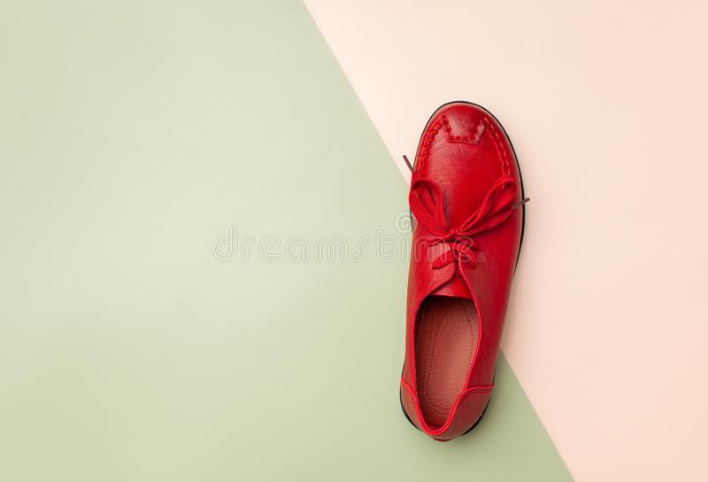 Red women`s leather autumn moccasin on pink and green background stock image
