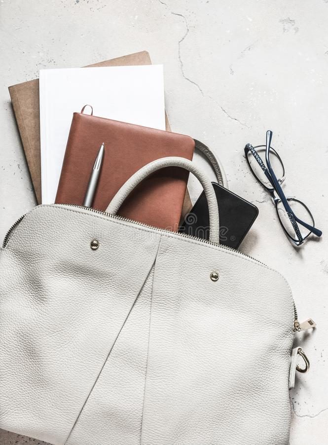 Women`s bag with office accessories on a light background, top view.  stock images