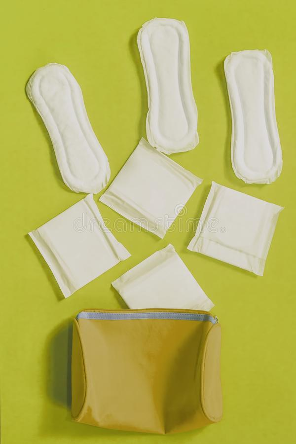 Women`s bag and sanitary napkins on blue background. Women`s bag and sanitary napkins on the blue background stock photo