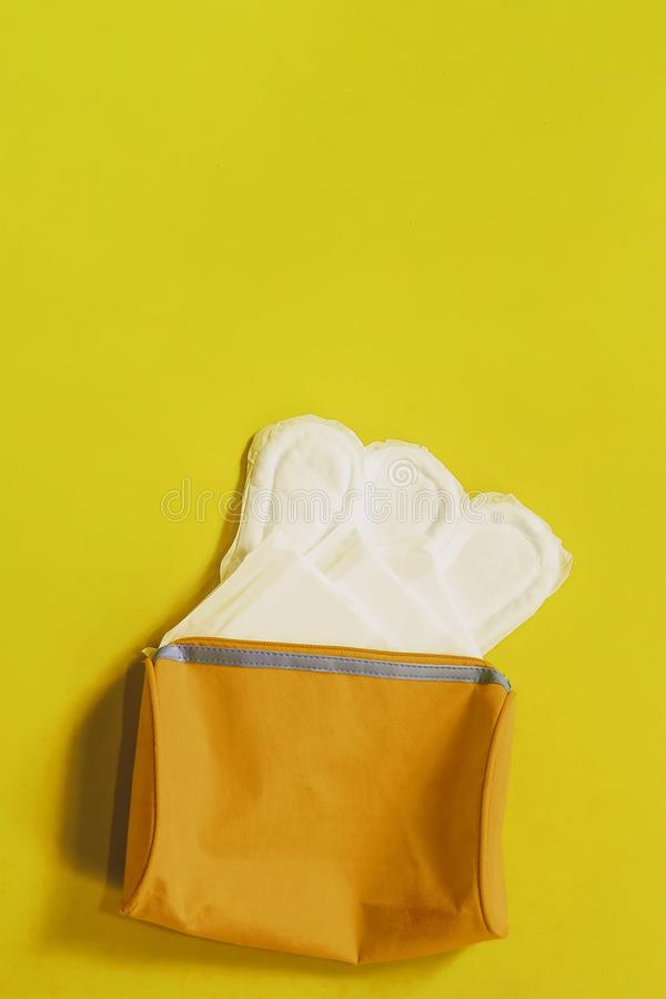 Women`s bag and sanitary napkins on blue background. Women`s bag and sanitary napkins on the blue background royalty free stock photos