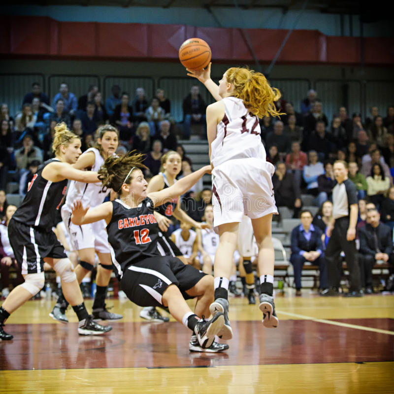 Women's Basketball. Carleton's Elizabeth Roach (centre) is sent crashing to floor whilst trying to block a shot by Ottawa's Catherine Traer (right) during the stock image
