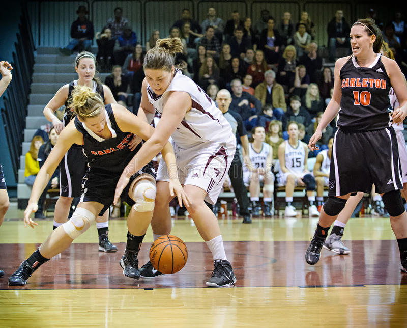 Women's Basketball. Carleton's Elizabeth Roach (left) and Ottawa's Jenna Gilbert (right) battle for the ball during the OUA East Final on March 2 2013 in Ottawa royalty free stock photo