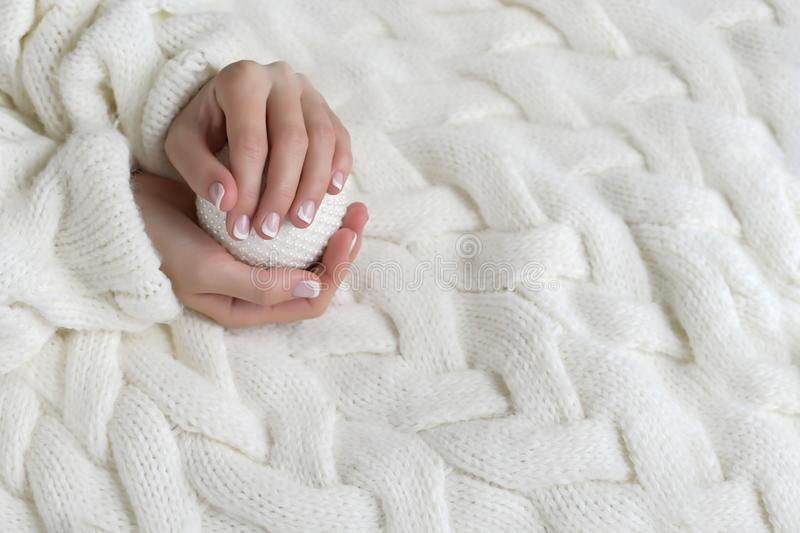 Women`s beautiful hands with French manicure on the background of a white warm sweater. With New Year ball royalty free stock photography