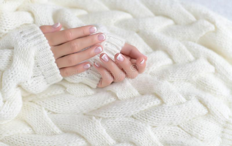 Women`s beautiful hands with French manicure on the background of a white warm sweater. Woman`s hand with French manicure isolated on white background stock photo