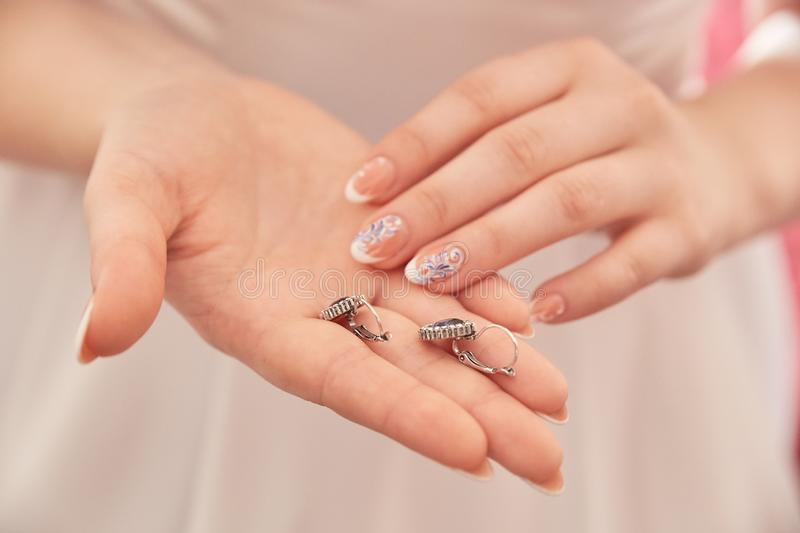 Women`s beautiful hands hold wedding rings royalty free stock photo