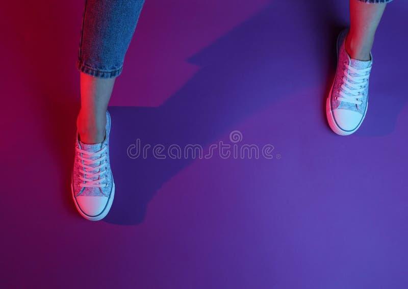 Women& x27; s benen in jeans en tennisschoenen stock afbeelding