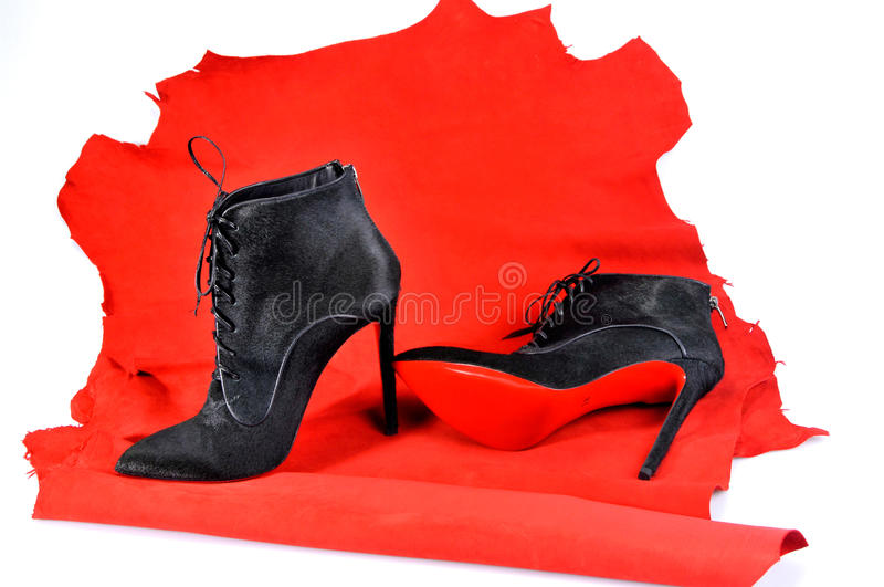 Women`s black ankle boots handmade on a piece of material from the red skin. royalty free stock photography