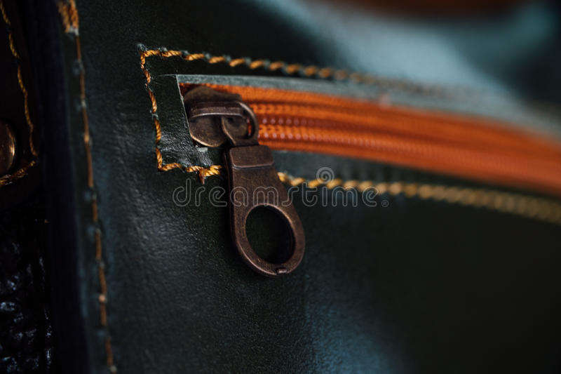 Women`s black purse with orange zipper close-up, stitch.Macro fragment of a leather bag or purse. royalty free stock photo