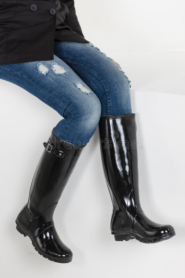 Women& x27;s black rubber boots with blue jeans stock photography