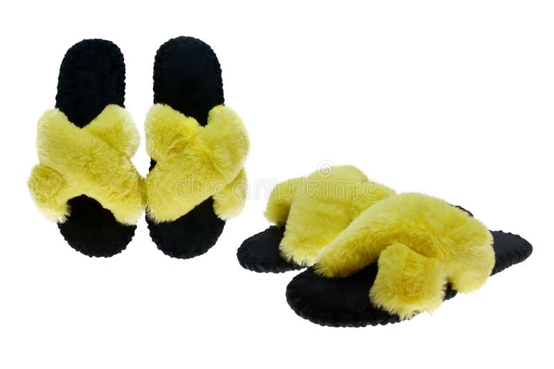 Women`s black slippers with yellow fluffy fur trim. Comfortable home shoes for relaxation. Isolated, white background royalty free stock images