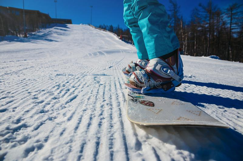 Women`s boots and snowboard snowboarder in the snow on the mountain stock photos