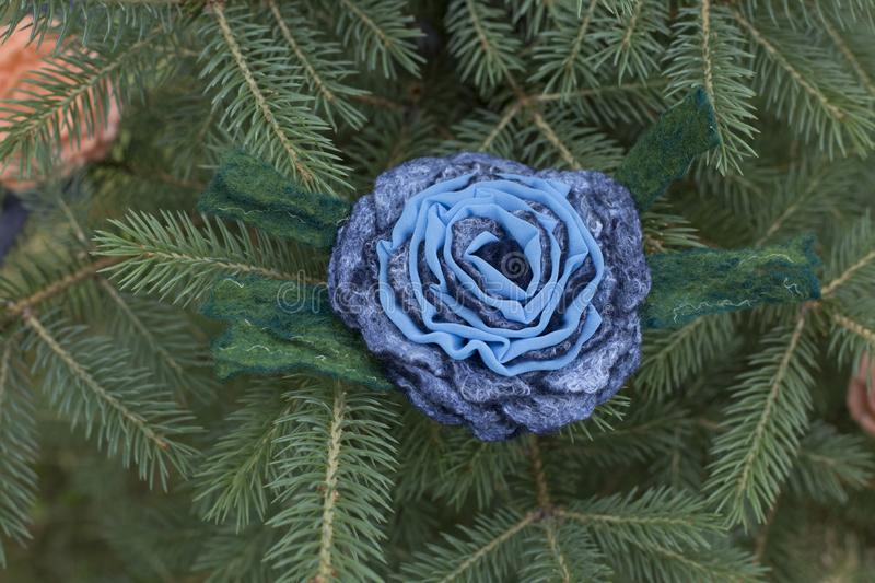 Women`s brooch of fulled wool on branches of green spruce stock photography