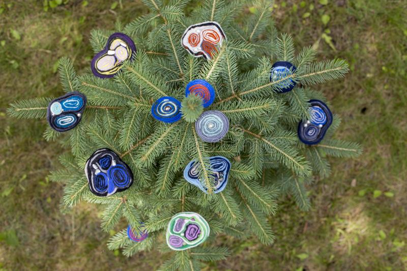 Women`s brooch of fulled wool on branches of green spruce. stock photo