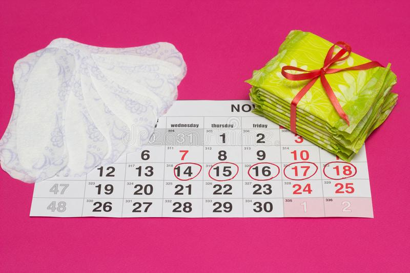 Women`s calendar on which the hygiene and daily pads, gynecology, pink background, marked days stock photo