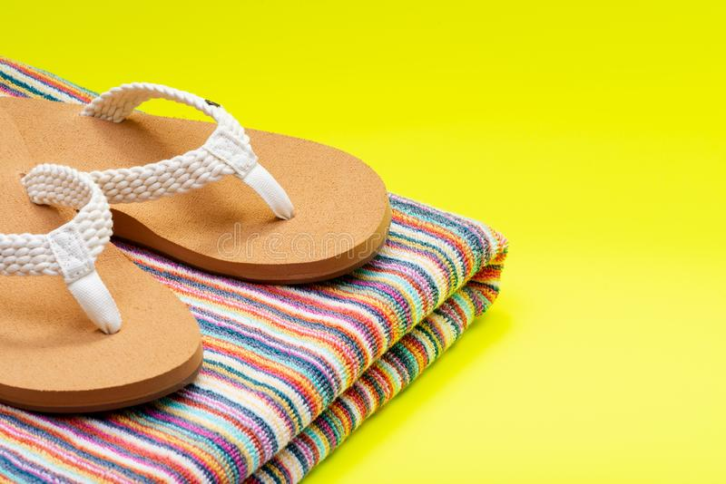 Women`s Causal Braided natural color Beach Day Flip Flops and folded colorful striped beach towels on bright yellow royalty free stock image