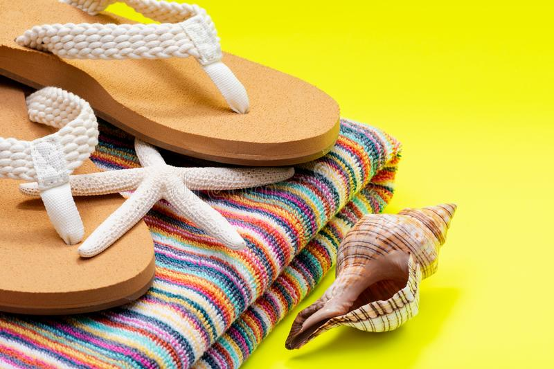 Women`s Causal natural color Beach Flip Flops and Colorful Striped Beach Towel decorated with White Finger Starfish and Seashells royalty free stock photo