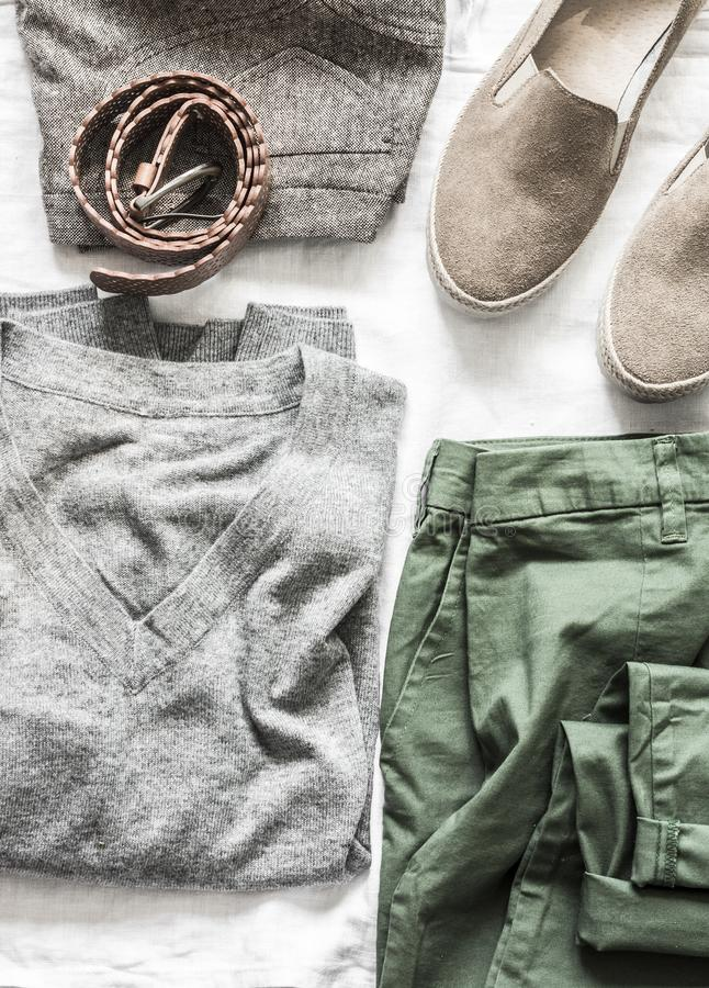 Women`s clothing on a light background, top view. Autumn women`s clothing -  suede shoes, pullover, skirt, pant, belt. Fashion stock photography