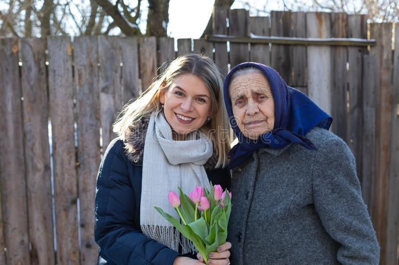 Women`s day celebration. Young women giving a bouquet of pink tulips to her elderly grandmother  on Women`s day, 8th of March. Love, care, gift, togetherness stock photo
