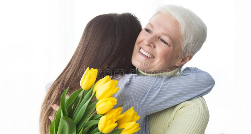 Women`s day. Daughter greeting her mother, giving flowers stock image
