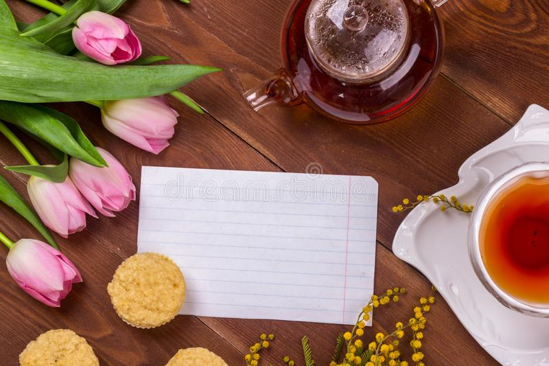 Women& x27;s day greeting card with tulips, mimosa, tea and cupcakes on brown wooden background royalty free stock image