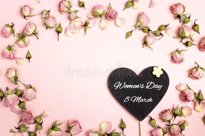 Women`s Day greeting message on heart-blackboard with small dry. Roses on pink background. Place for text. Flat lay, top view stock images