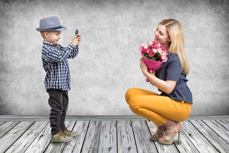 Little boy taking pictures on a mobile phone your mom with a bouquet of roses.Spring, concept of family vacation. Women`s day,moth royalty free stock photo