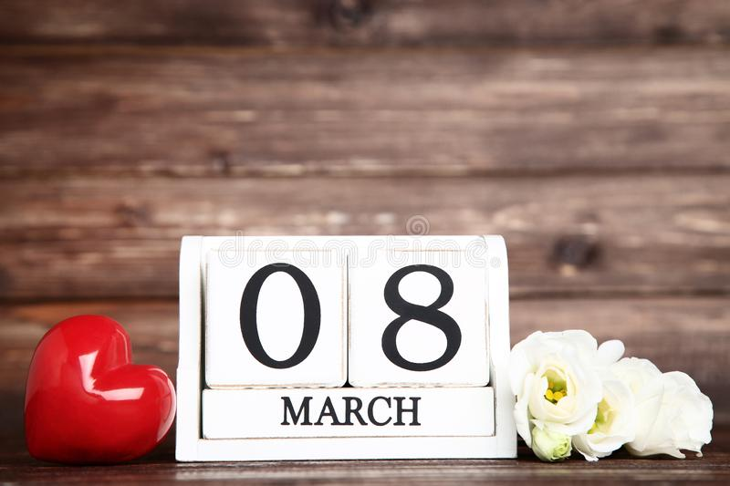 Women`s Day on wooden calendar. With eustoma flowers and red heart royalty free stock photography