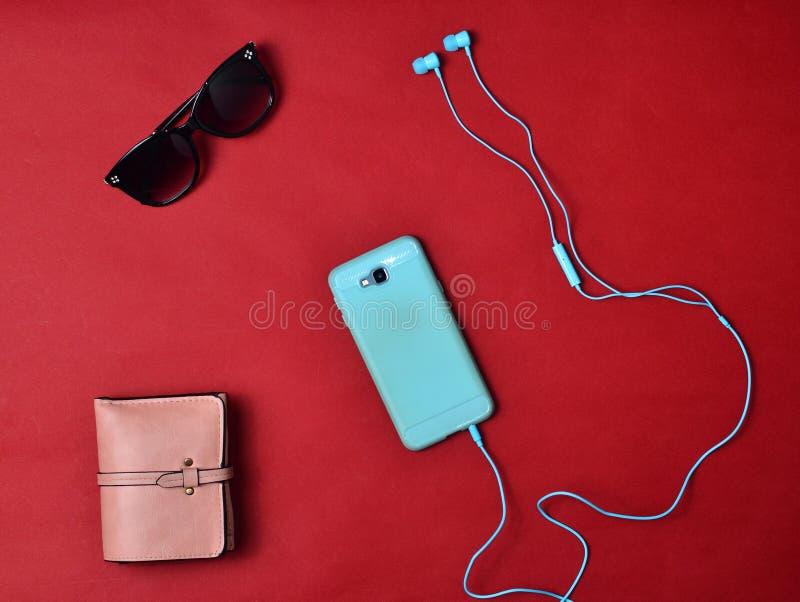 Women& x27; s de toebehoren zijn gevoerd op een rode achtergrond Smartphone, hoofdtelefoons, portefeuille, zonnebril Vlak leg stock afbeeldingen