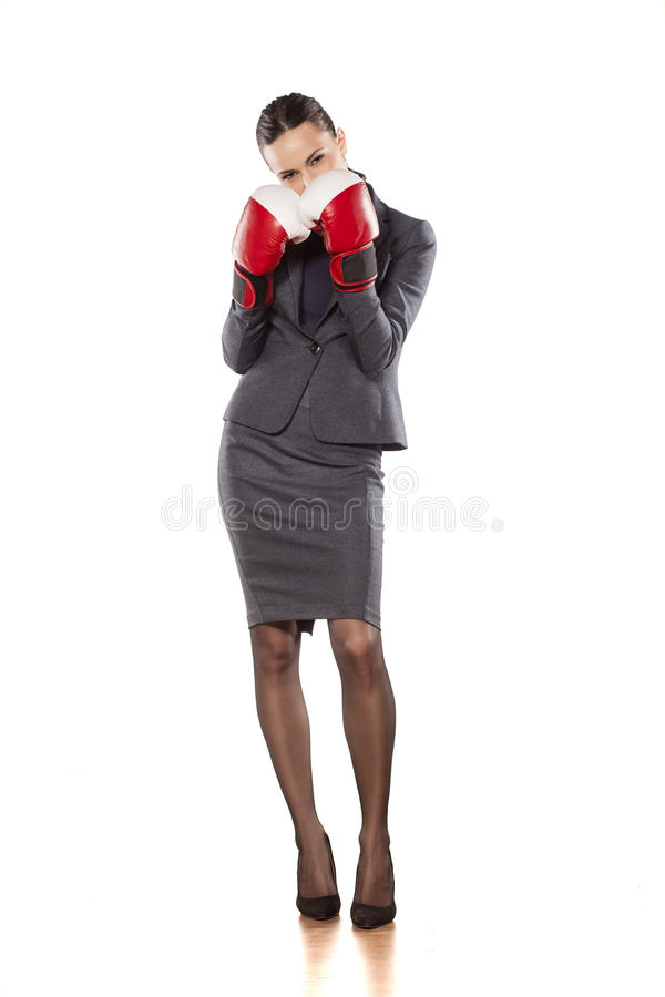 Women's defence. Portrait of an angry business woman with boxing gloves royalty free stock images