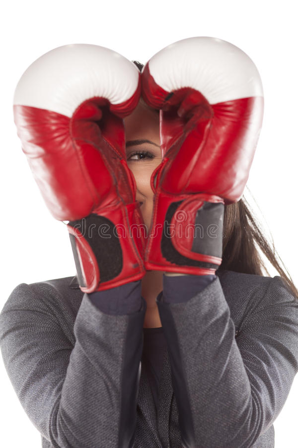 Women's defence. Woman peeking through boxing gloves set in heart shape royalty free stock images