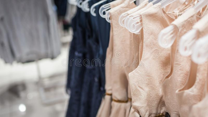 Women`s dresses on hangers in a clothing store stock images