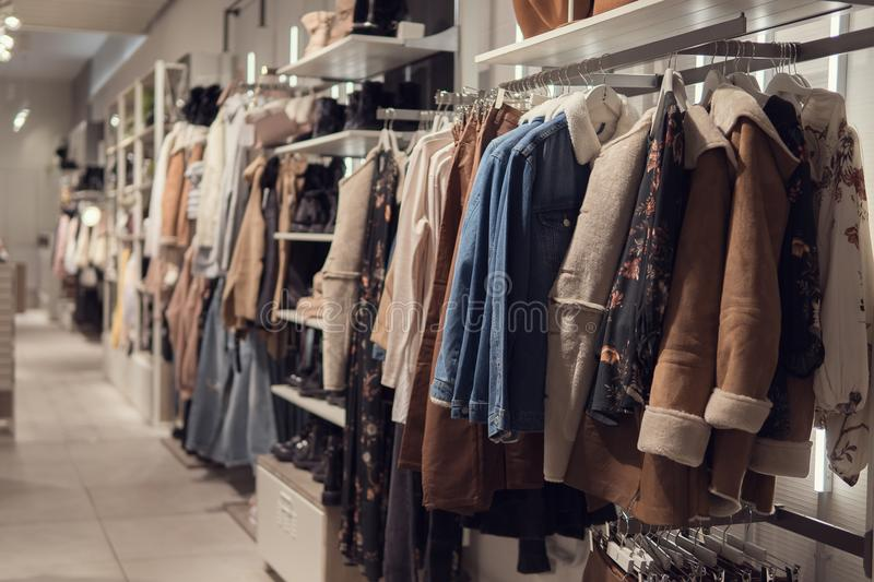 Women`s dresses and jacket on hangers in a retail shop. stock image