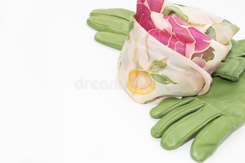 Women`s expensive silk scarf and green leather gloves royalty free stock photo